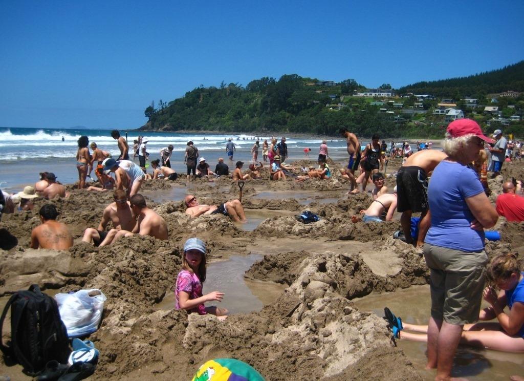 "hot water beach, Coromandel Peninsula, New zealand, people sitting in their ""natural hot spas"""
